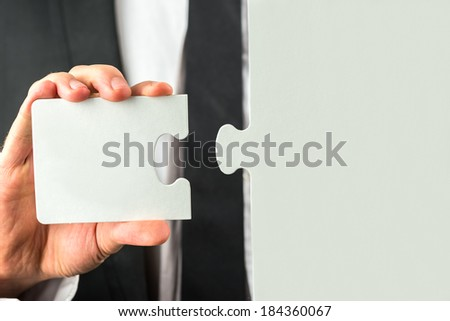 Businessman holding the missing piece to complete the puzzle in his hand conceptual of the solution to a problem or completing a task.