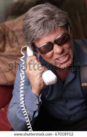 Businessman holding the phone upside down - stock photo