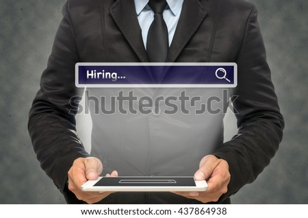 """Businessman holding the tablet with browsing of Internet searching """"Hiring""""bar on the wall background, Internet concept - stock photo"""