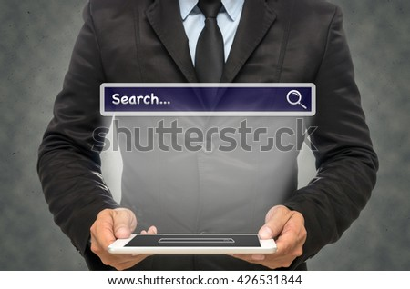 "Businessman holding the tablet with browsing of Internet searching ""search"" bar on the wall background, Internet concept"
