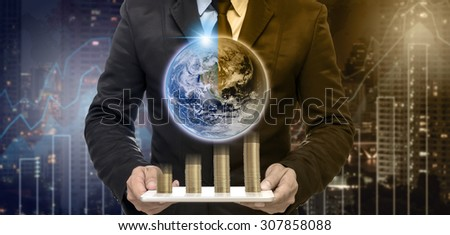 Businessman holding the tablet with earth and stack of golden coins on Trading graph on the cityscape at night and world map background,Elements of this image furnished by NASA - stock photo