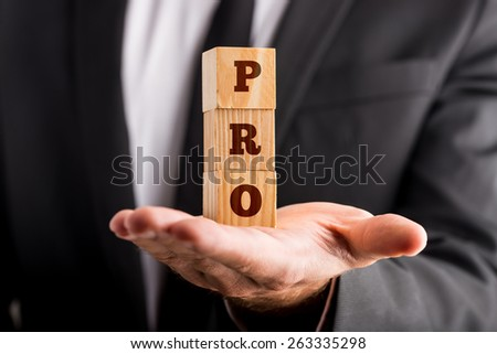 Businessman holding three wooden cubes stacked on the palm of his hand reading a PRO sign. Conceptual of professionalism and success. - stock photo