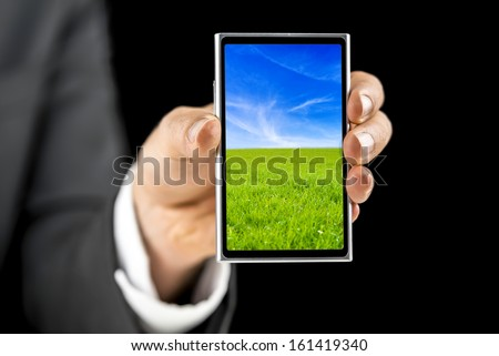 Businessman holding touch screen mobile phone with beautiful screensaver.