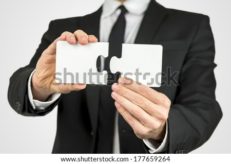 Businessman holding two blank white puzzle pieces in his hands conceptual of solving a problem, growth and development. - stock photo