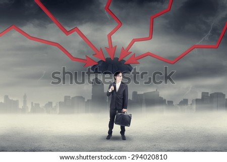 Businessman holding umbrella with declining arrows pressing the umbrella - stock photo