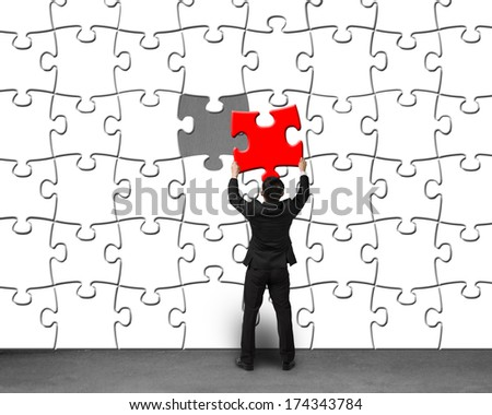 Businessman holding unique red puzzle assembling to white puzzles on concrete wall