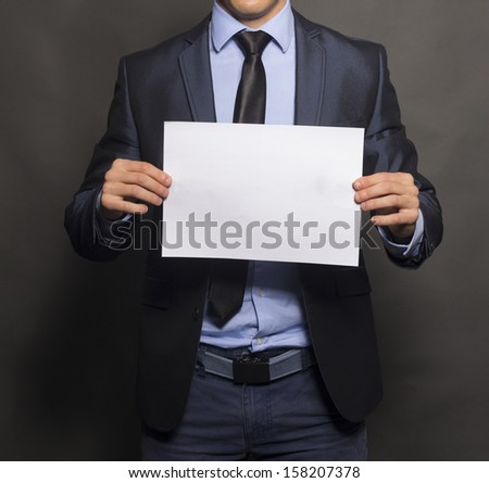 Businessman holding up a blank sign with room for adding text. Vertical shot. Isolated on gray. - stock photo
