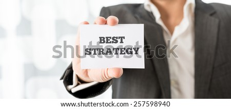 Businessman holding up a small white card saying Best Strategy in a conceptual image of business planning and research, close up of his hand. - stock photo