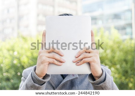 Businessman holding up a tablet in front of his face