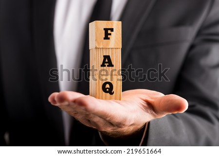 Businessman Holding Vertically Stacked Blocks Spelling FAQ in Palm of Hand. - stock photo