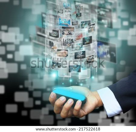 Businessman holding virtual phone - stock photo