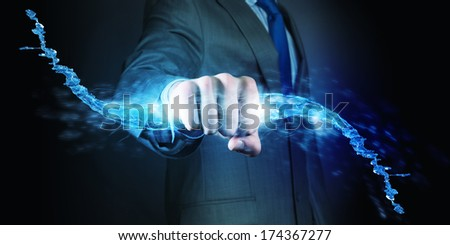 Businessman holding water splash in fist. Power and control