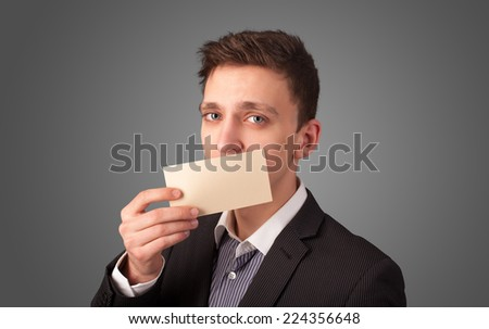 Businessman holding white card at front of her lips with copy space on gradient background - stock photo