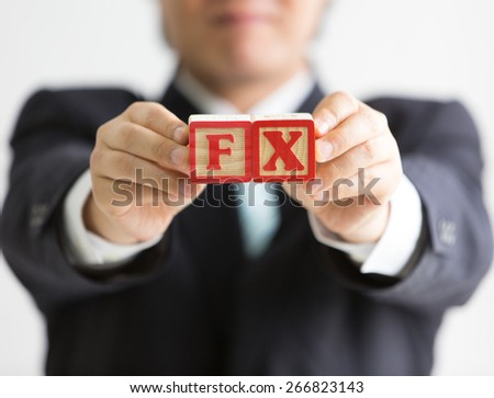 Businessman holding wooden blocks with etched letters F and X (abbreviation for foreign exchange market)