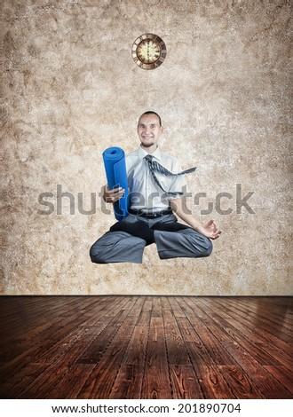 Businessman holding yoga mat and doing Levitation in lotus pose in the yoga hall with clock on the wall
