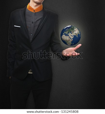 Businessman holds Earth in a hand. Elements of this image furnished by NASA. - stock photo