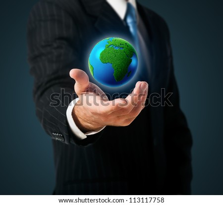 Businessman holds green Earth in a hand - stock photo