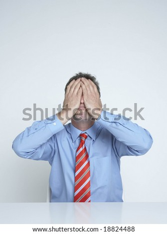 businessman holds his face in his hands