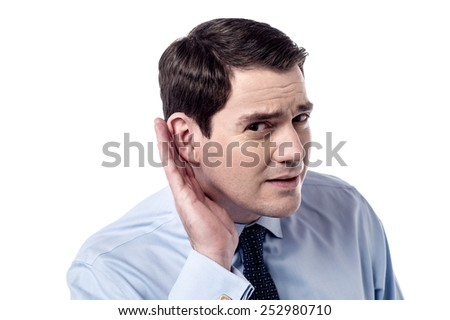 Businessman holds his hand near ear, listens closely. - stock photo