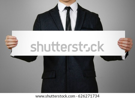Businessman holds in hands a long, narrow paper. Empty for your text. Isolated on gray background