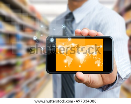 businessman holds mobile phone showing the world map and connected dot