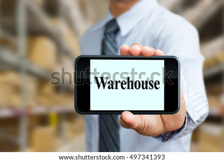 businessman holds mobile phone showing warehouse wording