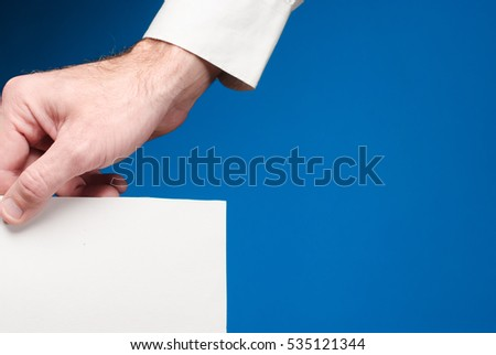 businessman holds paper in hand