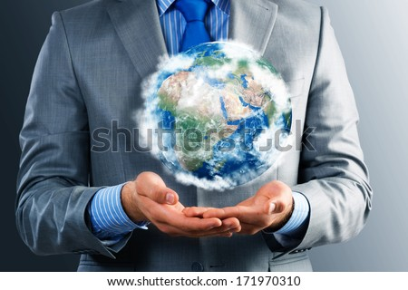 businessman holds up a planet Earth. Elements of this image furnished by NASA - stock photo