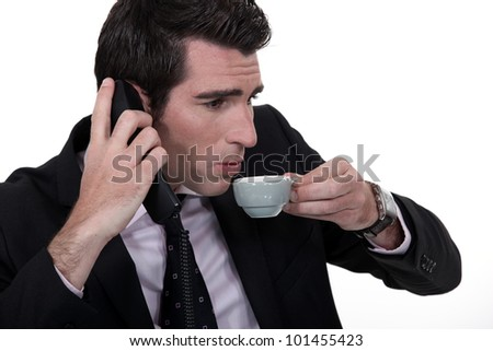 Businessman hurriedly trying to talk on the phone while drinking a cup of coffee