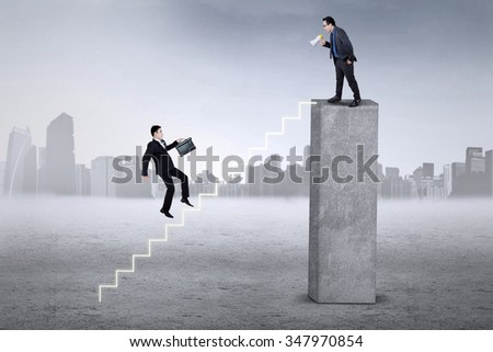 Businessman hurry up stepping the stairs after called by his leader from the top - stock photo