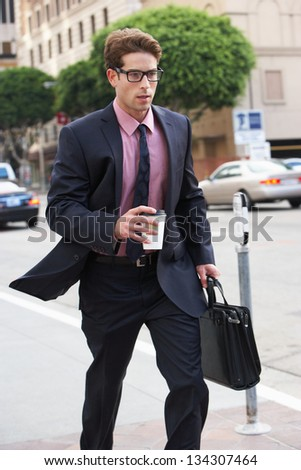 Businessman Hurrying Along Street Holding Takeaway Coffee - stock photo