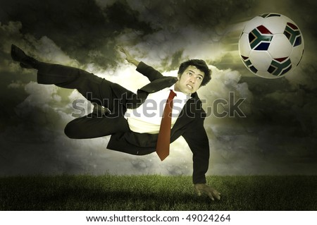 Businessman in a acrobatic pose kicking a soccer ball in a stormy field - stock photo