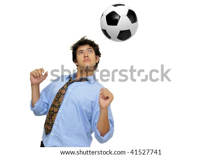 Businessman in a acrobatic pose with a soccer ball isolated in white