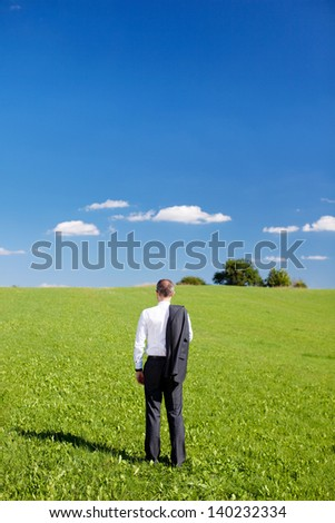 Businessman in a green field standing with his back to the camera and jacket slung over his shoulder looking out over the countryside