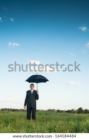 Businessman in a green field with black umbrella. - stock photo