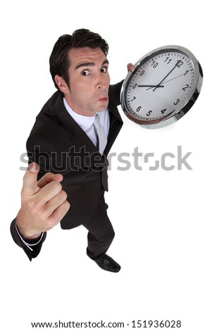 businessman in a hurry holding a huge clock - stock photo