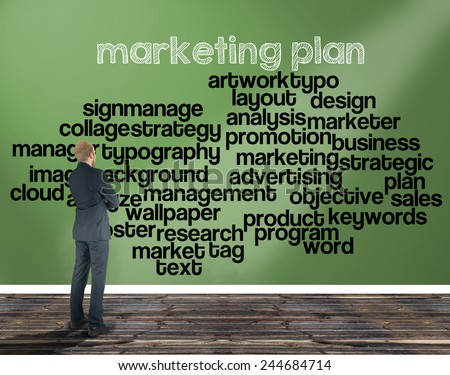businessman in a room looking at a wall of which is the wordcloud related to marketing plan - stock photo