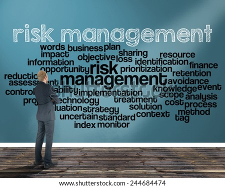 businessman in a room looking at a wall of which is the wordcloud related to risk management - stock photo