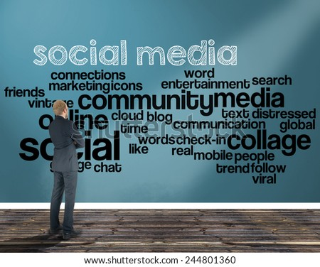businessman in a room looking at a wall of which is the wordcloud related to social media - stock photo