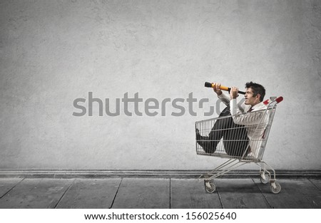 businessman in a shopping cart looks with telescope