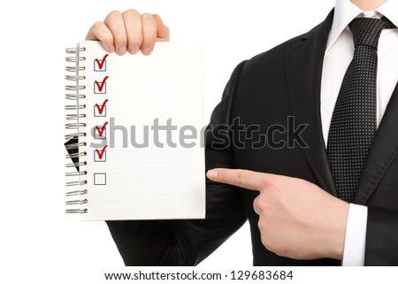 businessman in a suit and tie holding a notebook or piece of paper - stock photo