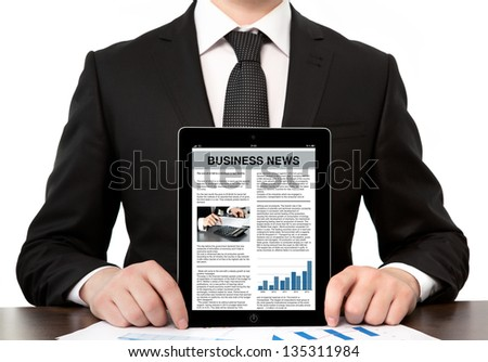 businessman in a suit at the office holding a computer tablet with business news on screen - stock photo