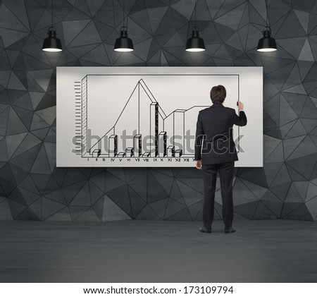 Businessman in a suit drawing a graph - stock photo