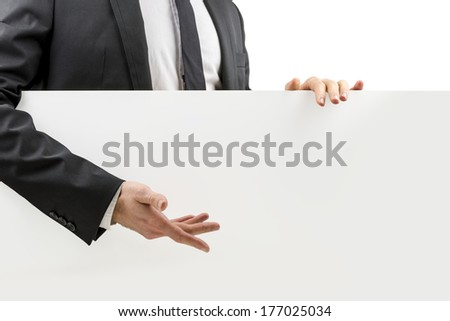 Businessman in a suit gesturing to a blank white board with his hand that he is standing behind and holding with copyspace for your advertising or text, closeup torso view. - stock photo