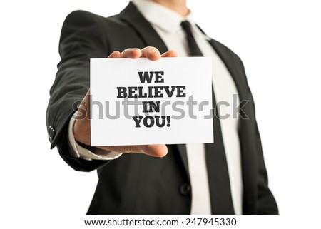 Businessman in a suit holding up a business card with motivational message We believe in you. - stock photo