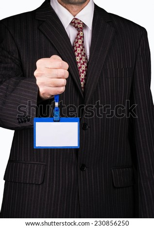 Businessman in a suit holds a blank badge - stock photo