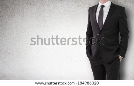businessman in a suit holds hands in pockets