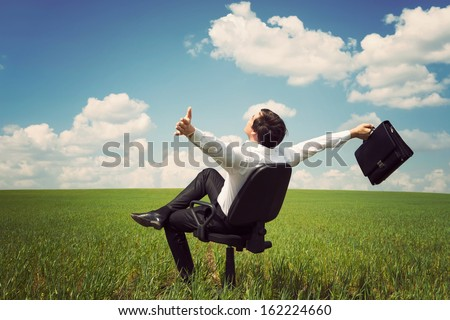 businessman in a suit in a green field with a blue sky sitting on an office chair and waving his arms - stock photo