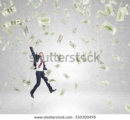 businessman in a suit jumping happily with his hand up, money falling from above, concept of success - stock photo