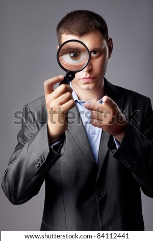 businessman in a suit looking through a magnifying glass